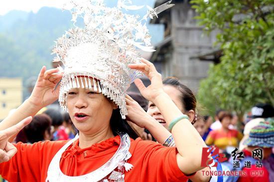 侗族银饰吸引游客试穿。