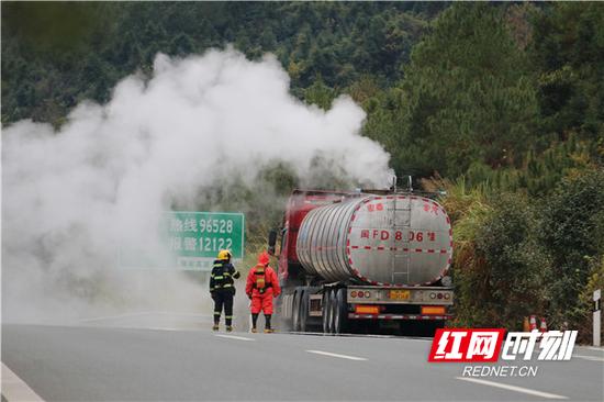 消防救援人员冒着危险上前勘查危化运输车危化品泄露情况。