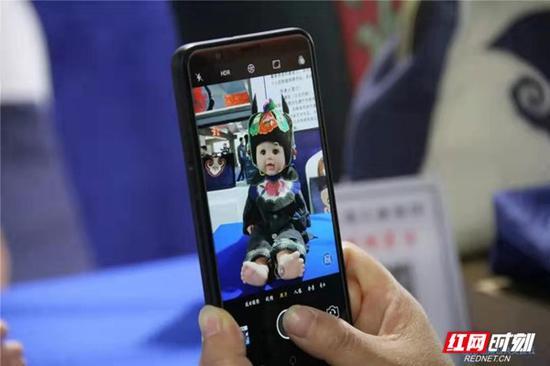 一名参观者用手机拍下自己喜爱的大布江拼布绣作品。