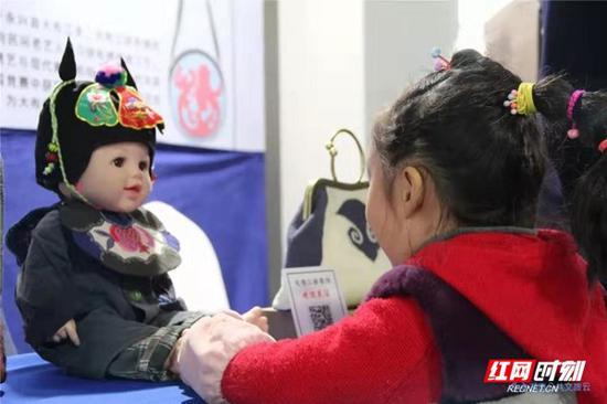 大布江拼布绣展区一位小朋友被一个作品深深吸引住了。