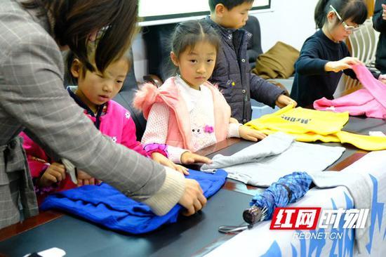 在志愿者的指导下,孩子们学会归纳衣物。