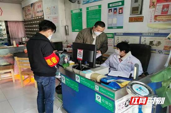 2月3日,谭伟智(中)在药店检查进货单据。
