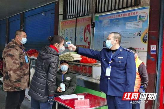 2月3日,张志云(前排右一)在岳阳平江县西街菜市场为经营户测量体温。