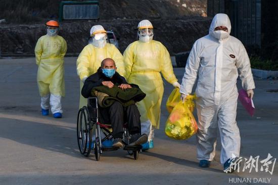 (2月22日,湖北省黄冈市红安县中医医院,湖南医疗队医护人员送90岁的患者走出医院。)