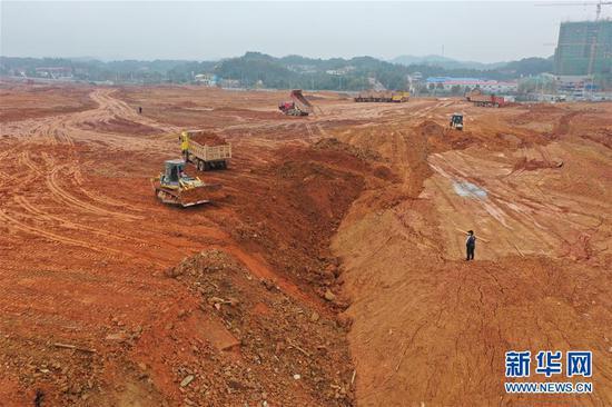 这是2月21日拍摄的长沙高新区319国道南侧的中联重科智慧产业城工地,推土机和渣土车在进行填埋作业(无人机照片)。 新华社记者 姚羽 摄
