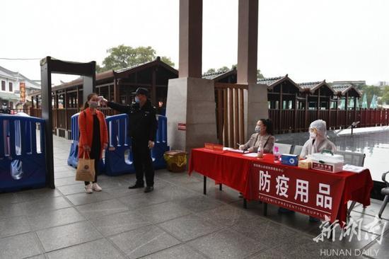 (2月27日,南岳衡山景区恢复开放,工作人员为游客测量体温、登记信息。)
