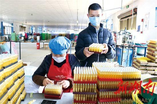 (2月27日上午,浏阳市两型产业园企业湖南倬亿打火机制造有限公司生产车间内,贫困户周晓玲与其儿子正在忙着换板、装机头。该市113个就业扶贫车间(基地)正在陆续复工。)