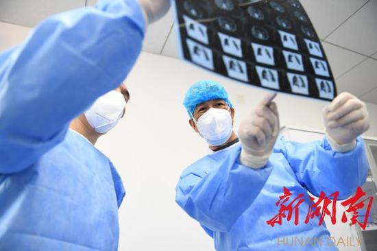 2月23日,湖北省黄冈市英山县人民医院,65岁的李新中仔细查看患者的CT检查结果。湖南日报记者 辜鹏博 朱玉文 摄