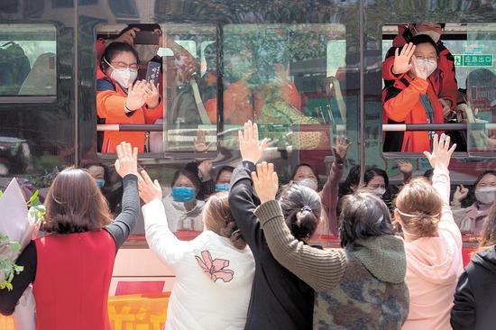 3月17日,武汉市江夏区纽宾凯楚悦酒店,江苏省第二批援鄂医疗队140余名队员撤离驻地,挥别欢送的人群,前往武汉天河机场乘包机返回江苏。 (湖北日报全媒记者 蔡俊 摄)