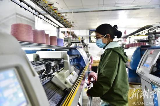 (3月2日,蓝山县归雁创业园泰兴服饰有限责任公司,工人在忙碌作业。杨雄春 摄)