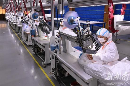 (3月3日,湖南梦洁家纺股份有限公司,工人在加紧生产医用防护服。湖南日报记者 童迪 摄)