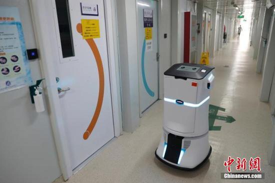 """3月30日,在尚未收治患者的北京小汤山医院""""清洁区""""内,消毒机器人正在走廊进行消毒。中新社记者 韩海丹 摄"""