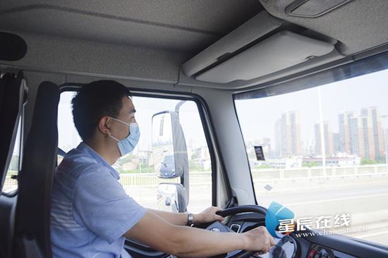 (戴伯钧驾驶垃圾装运车行驶在路上。)