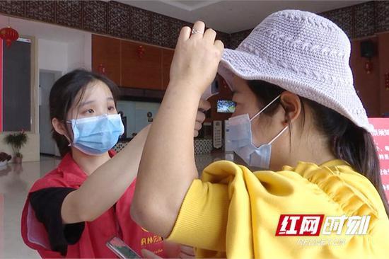 景区内工作人员检查游客体温是否正常。
