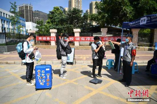 资料图:5月11日,云南一高校返校学生间隔排队、扫码进校园。中新社记者 刘冉阳 摄