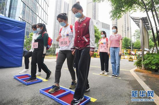 幼儿园老师模拟幼儿开园,入园前将鞋底消毒。