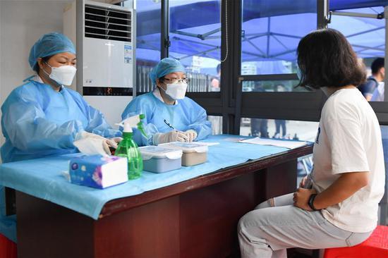 医务人员在体温复核区模拟询问考生(右)身体情况。新华社记者 薛宇舸 摄