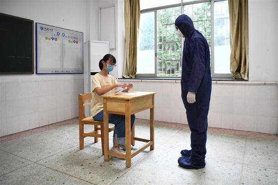 工作人员(右)模拟为发热考生安排考试座位。新华社记者 薛宇舸 摄