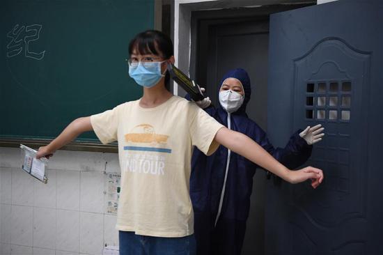 工作人员(右)模拟为发热考生进行安检。新华社记者 薛宇舸 摄