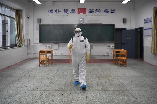 开福区疾病预防控制中心工作人员在模拟为隔离备用考室消杀。新华社记者 薛宇舸 摄