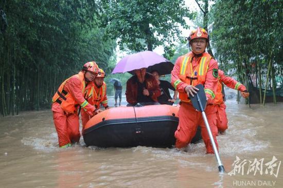 (7月8日,张家界永定区西溪坪街道禾家村,消防指战员在转移被困群众。通讯员 吴杰 摄)