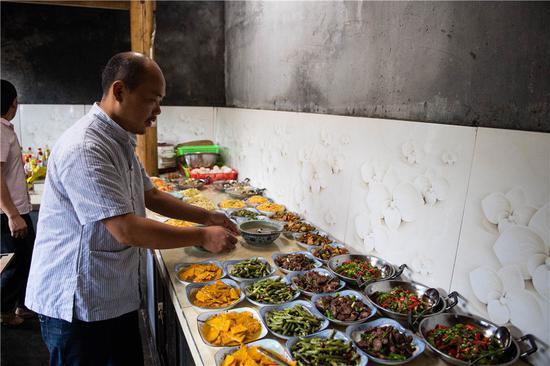 在湘西十八洞村,杨正邦在自家开的饭店厨房里帮忙(6月30日摄)。新华社记者 陈思汗 摄