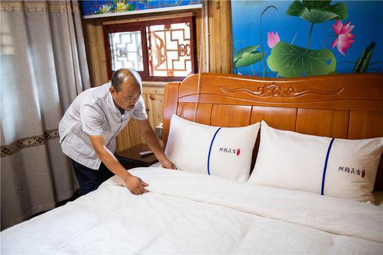 在湘西十八洞村,杨正邦在整理民宿(6月30日摄)。新华社记者 陈思汗 摄
