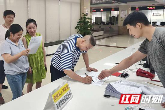 退役军人排队办理社保补缴手续,并签字缴费。