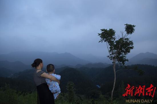 """(母亲抱着""""瓷娃娃""""曾宏杰,眺望山外的世界。唐俊 卜云 摄)"""