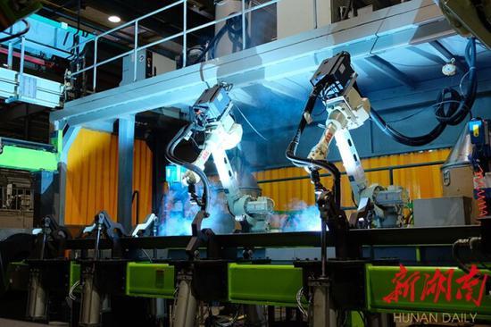 """(7月29日,位于常德高新区的中联建起智能化生产车间,机器人在焊接作业。企业发展,""""智""""字当头。去年,智能制造引领中联建起跻身百亿企业序列。卜云 摄)"""