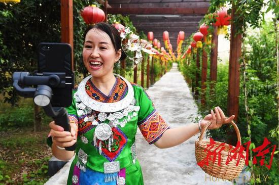 (8月12日上午,苗家阿妹熊丽艳手机直播推介当地土特产和旅游景点。)