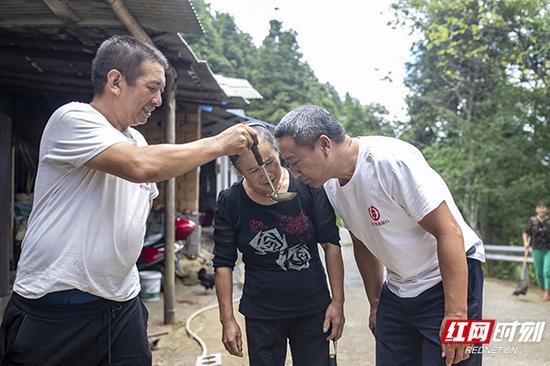 同事过来看头锅山胡椒油,蒋爱文舀了一勺,让同事闻闻油的香味。