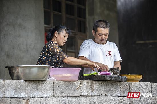 把同事的问题解决后,蒋爱文帮爱人一起做饭。