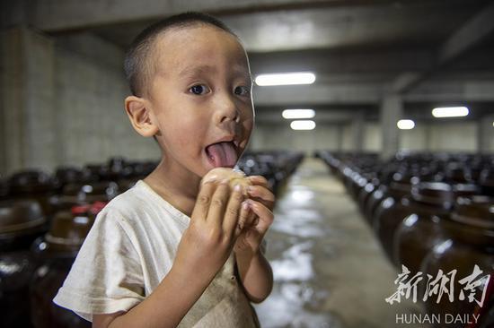 (8月21日,永州市冷水滩区麦子园村,小孩子舔吃陶土坛里腌制出来的大蒜。 湖南日报·华声在线记者 辜鹏博 摄)