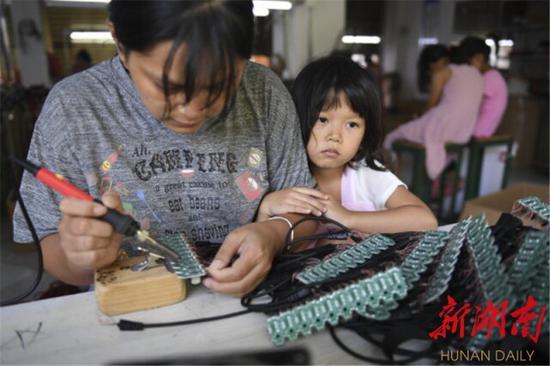 8月30日,江华瑶族自治县水口镇如意社区扶贫工厂,4岁小女孩李欣宜依偎在妈妈冯秀芳身边。冯秀芳以前在广东务工,得知家乡扶贫工厂可以上班,她选择回乡。既能上班,也能照顾家人。