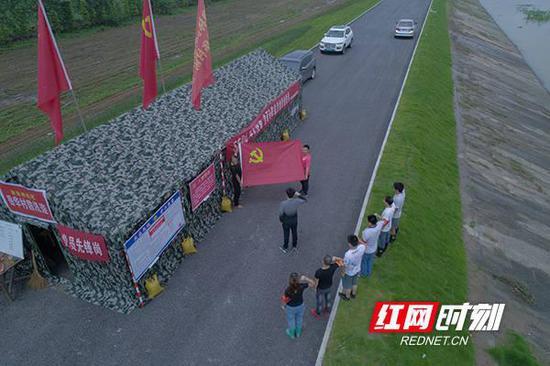 岳阳市君山区柳林洲街道办事处责任堤段党旗飘扬,新发展的预备党员在宣誓。