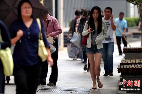 """白露PC配图。""""白露身不露"""" ,北京街头行人""""混搭装""""出行。中新网记者 金硕 摄"""