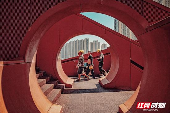 """梅溪湖""""中国结""""步行桥。摄于8月17日11:18,通过步行桥的是三三两两的工人,顶着大太阳去工作。"""