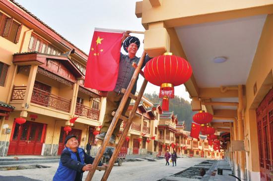 凤凰县禾库镇易地扶贫搬迁安置区,村民吴玉题在挂红旗和灯笼。他从禾库社区搬到安置区,政府给他安排了公益性岗位。