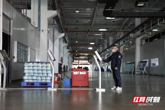 上岗前,吴新平在指纹机上打卡。身后的工厂厂房里一辆自动运输机器人车把各种零件运输到指定地点。