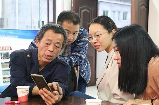桑植县走马坪白族乡村民通过手机给记者展示现在的生活场景。人民网张桂贵摄