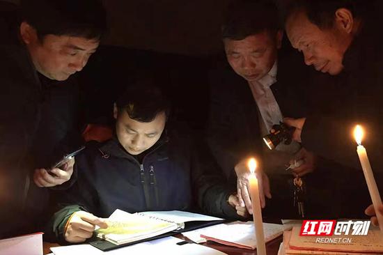 停电的冬夜,工作人员借着烛光在金江镇罗家村连夜调研。