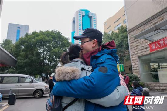 湖南省流行病学调查队队员与家人拥抱告别。