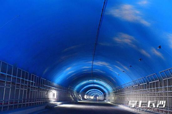 目前,麓景路南延线工程隧道顶部蓝天白云彩绘已喷涂完毕,正在进行防护板、机电安装等扫尾施工,预计本年6月实现完工。均为长沙晚报记者 王志伟 摄