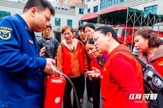 志愿者询问灭火器使用细节。