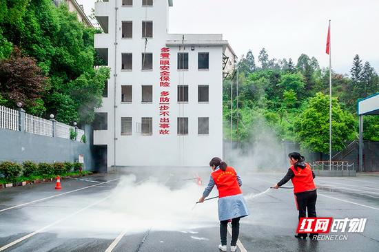 志愿者实践使用消防器材。