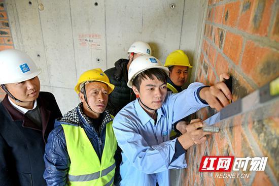 中国建筑五局总承包公司质量管理员邹彬。(前右一)
