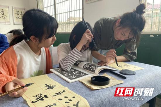谭世婷在指导学生练习书法。