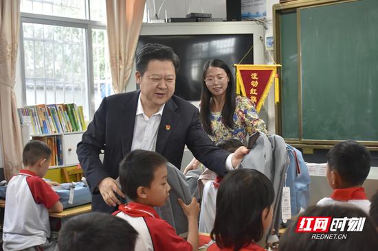 刘志仁向孩子们发放儿童节礼物。