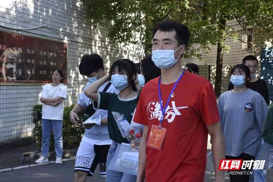 益阳市第十三中考点,送考员穿着满分T恤给孩子们加油。